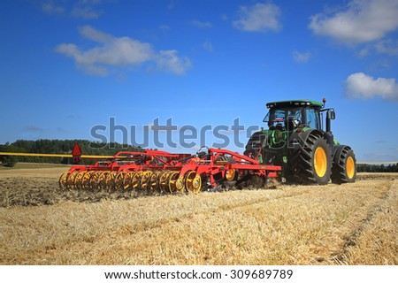 SALO, FINLAND - AUGUST 22, 2015: John Deere 8370R tractor and Vaderstad Opus 400 cultivator on field at Puontin Peltopaivat Agricultural Harvesting and Cultivating Show. - stock photo