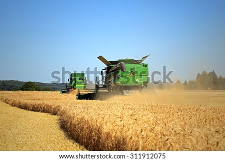SALO, FINLAND - AUGUST 22, 2015: Two John Deere modern Combines harvest barley at Puontin Peltopaivat Agricultural Harvesting and Cultivating Show. - stock photo