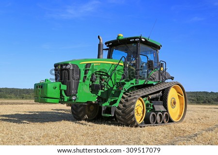 SALO, FINLAND - AUGUST 21, 2015: Unnamed farmer operates John Deere 8345RT tracked tractor on field at setting up of Puontin Peltopaivat Agricultural Harvesting and Cultivating Show.