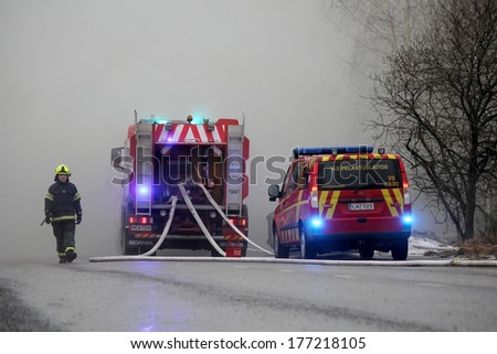 SALO, FINLAND - FEBRUARY 16, 2014: Firefighter emerges from heavy smoke at the fire scene of Salo Cement Plant, with two fire trucks on the street. - stock photo