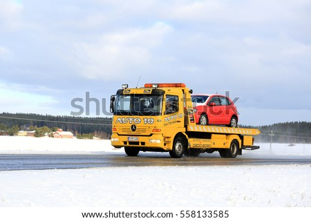 SALO, FINLAND - FEBRUARY 13, 2016: Yellow Mercedes-Benz tow truck carries a breakdown car in winter.