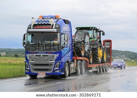 SALO, FINLAND - JULY 10, 2015: Volvo FH16 hauls John Deere machinery on gooseneck trailer. Volvo Trucks certify all engines for the diesel HVO. - stock photo
