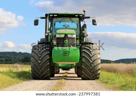 SALO, FINLAND - SEPTEMBER 6, 2014: John Deere 7280R agricultural tractor on a rural road by oilseed fields. The 7280R has 9.0 l DieselOnly PowerTech PVX engine. - stock photo