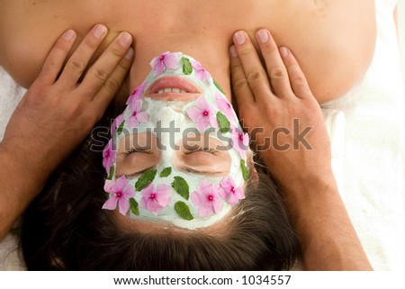 Salon Luxuries - A woman enjoys a therapeutic neck massage during a facial treatment  - landscape - stock photo