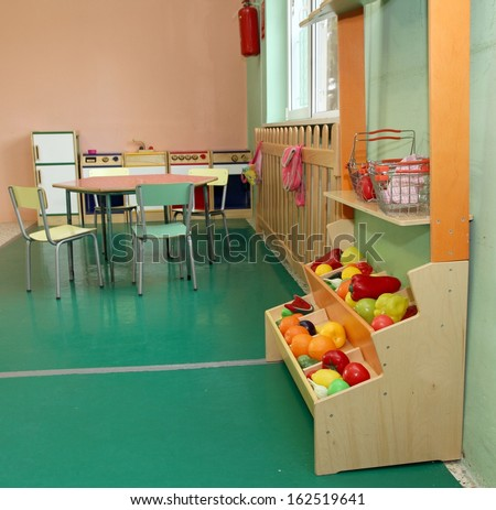 Salon of a nursery with stand of fruit and wooden kitchen toy