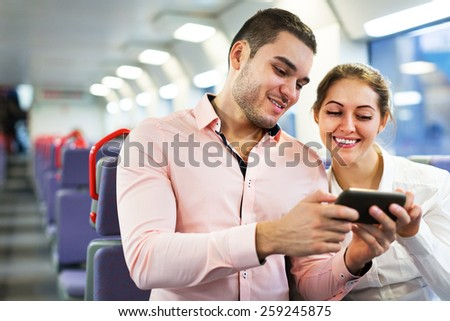Salon of the train with a happy young passengers using mobile phones - stock photo