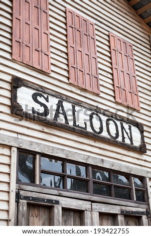 Saloon sign on western wooden building - stock photo