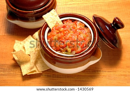 Salsa bowl with corn chips on a rustic wooden table - stock photo