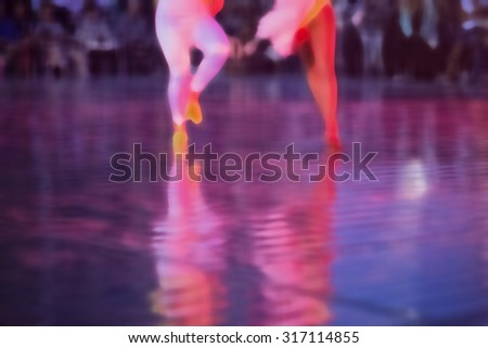 Salsa dancers dance in a competition, background blur with shallow depth of field bokeh effect - stock photo