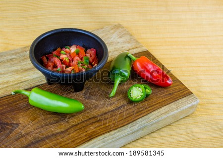 Salsa with jalapeno peppers, bell peppers, tomatoes on cutting board - stock photo