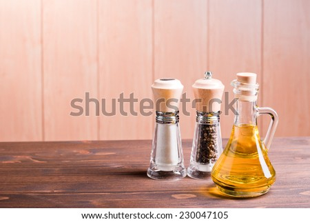 salt and pepper and sunflower oil on brown desk side view - stock photo