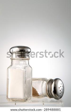 salt and pepper glass shaker - stock photo