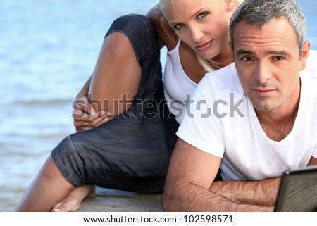 salt-and-pepper guy with laptop posing with younger girlfriend - stock photo