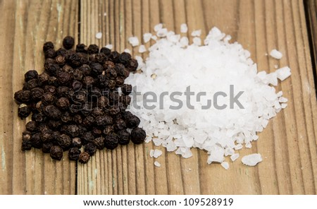 Salt and Pepper heaps on wooden background - stock photo