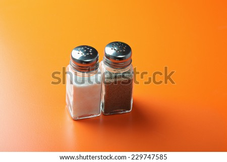 Salt and pepper in a glass containers over orange tabletop - stock photo
