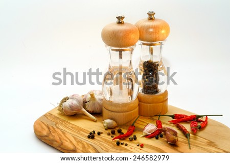 salt and pepper mill with ingredients around on wooden cutting board isolated on white background - stock photo