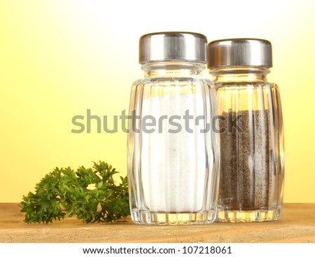 Salt and pepper mills and parsley on wooden table on yellow background