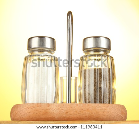 Salt and pepper mills, on wooden table on yellow background