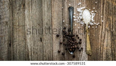 salt and pepper peas in silver spoons on wooden background - stock photo