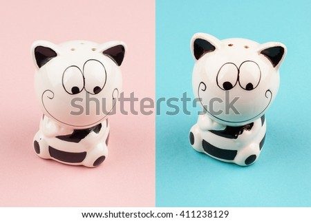 Salt and pepper. Seasoning to the dishes. Funny tableware. Salt shaker in the form of a cat on a pink background and the pepper pot in the form of a cat on a blue background - stock photo