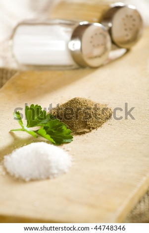 Salt and pepper shakers and small heaps. - stock photo