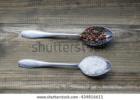 Salt and pepper. Two metal spoons with salt crystals and color peppercorns on wooden table - stock photo