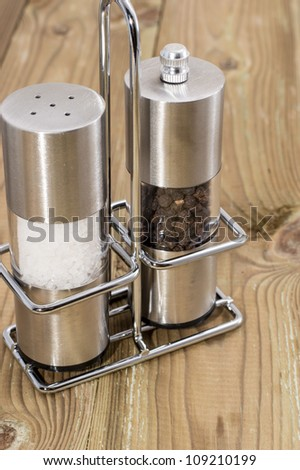 Salt- and Peppershaker on wooden background - stock photo