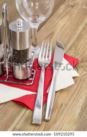 Salt- and Peppershaker with cutlery on wooden background - stock photo
