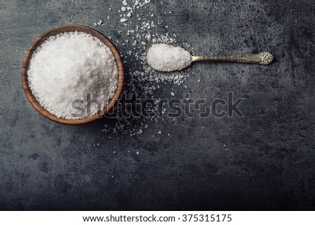 Salt. Coarse grained sea salt on granite - concrete  stone background with vintage spoon and woden bowl. - stock photo