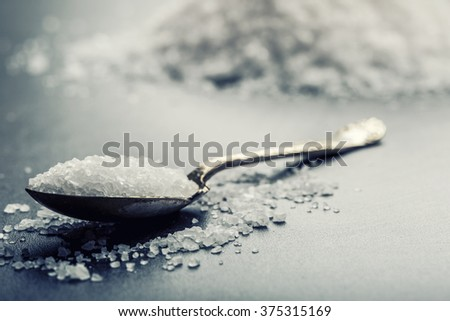 Salt. Coarse grained sea salt on granite - concrete  stone background with vintage spoon and wooden bowl. - stock photo