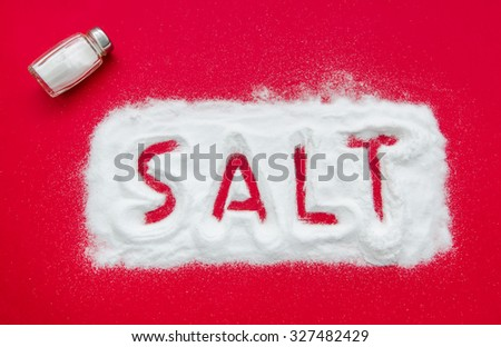 Salt concept text written on a red background with a shaker suggesting health concerns and problems produced by this ingredient