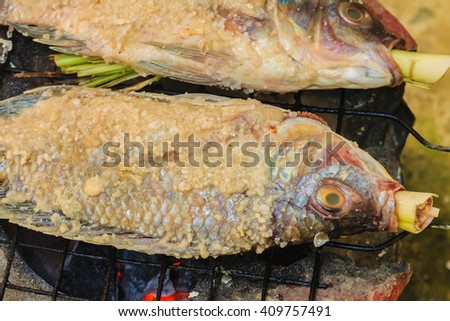 Salt Crusted Grilled Nile Tilapia Fish on Grate on charcoal - stock photo