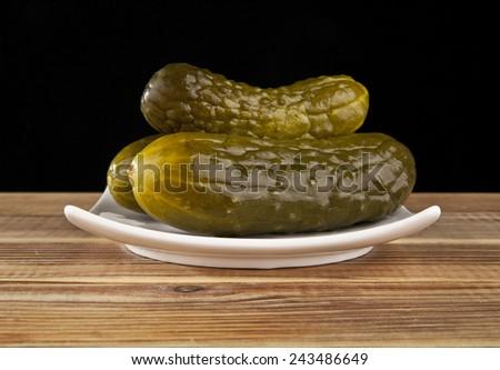 salt cucumbers on a black background - stock photo