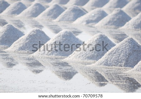 Salt fields with piled up sea salt in Thailand - stock photo