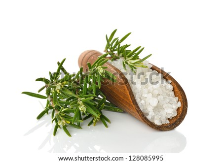 Salt in a wooden scoop and rosemary on a white background - stock photo