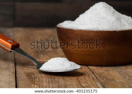 salt in bowl with spoon on the wooden table in kitchen - stock photo