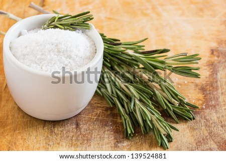 Salt in ceramic bowl with rosemary on wooden background. Selective focus.