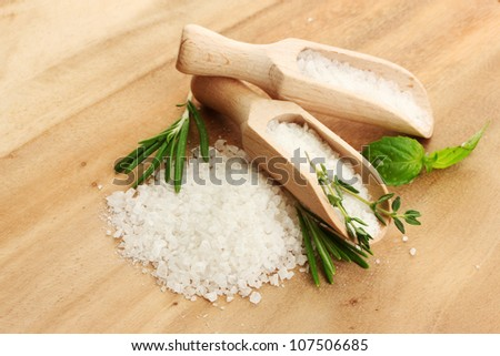 salt in shovels with fresh basil, rosemary and thyme on wooden background