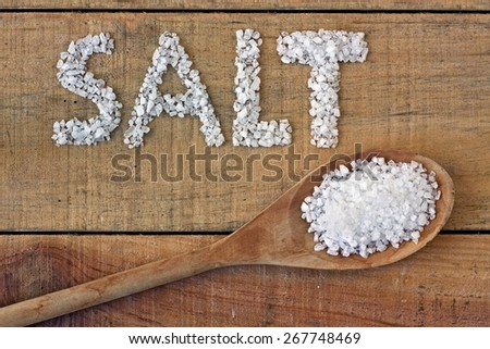 Salt in spoon on a wooden table - still life - stock photo