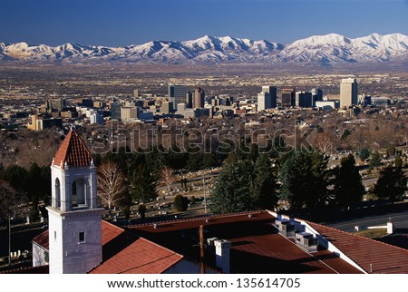 Salt Lake City and snow capped Wasatch Mountains in the background - stock photo