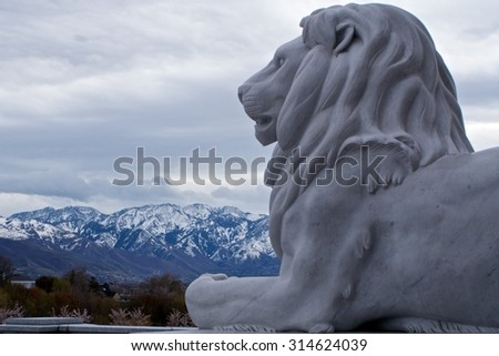 Salt Lake City State Capital Lion Statue with Snow capped Mountains in the Background - stock photo