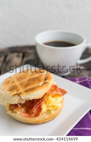 Salt muffin with scrambled eggs, bacon and cheese on white plate with dark coffee in white mug lying on wooden background. Unhealthy breakfast and coffee on purple dishtowel.