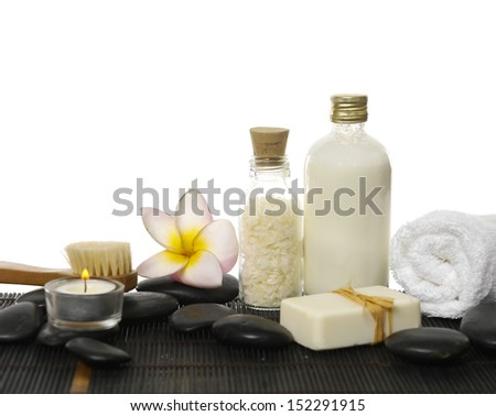 salt ,oil in glass, frangipani, towel ,candle ,soap on black pebbles
