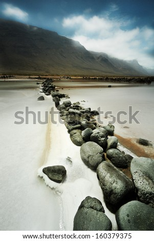 salt on a sunny day with high clouds with mountains in the background and rocks in the foreground row in Lanzarote, Canary Islands (Spain) - stock photo