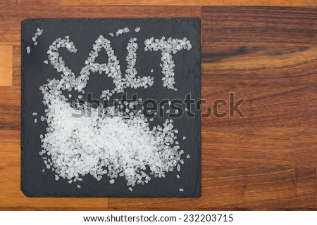 Salt on black plate with wooden background  - stock photo