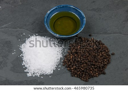 Salt, pepper and oil on a grey slate table