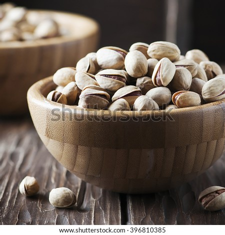 Salt pistachio nuts in the wooden bowl, selective focus and square image - stock photo