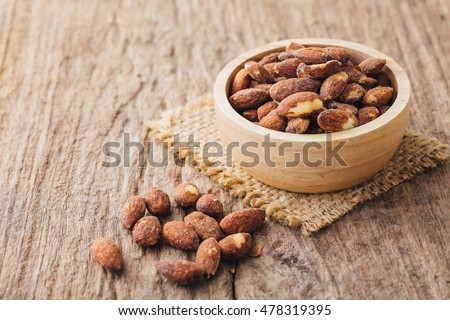 Salt roasted almond in wooden bowl on wooden table