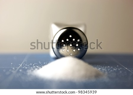 Salt shaker on wooden table - stock photo