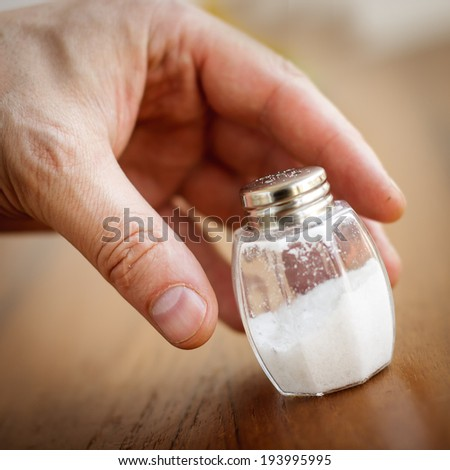Salt shaker taken by hand from wooden table - stock photo